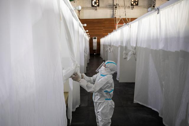A health worker in personal protective equipment draws the curtains of a makeshift room used by a coronavirus disease (COVID-19) patient in a quarantine facility in Manila, Philippines, April 15, 2021. Photo: Reuters