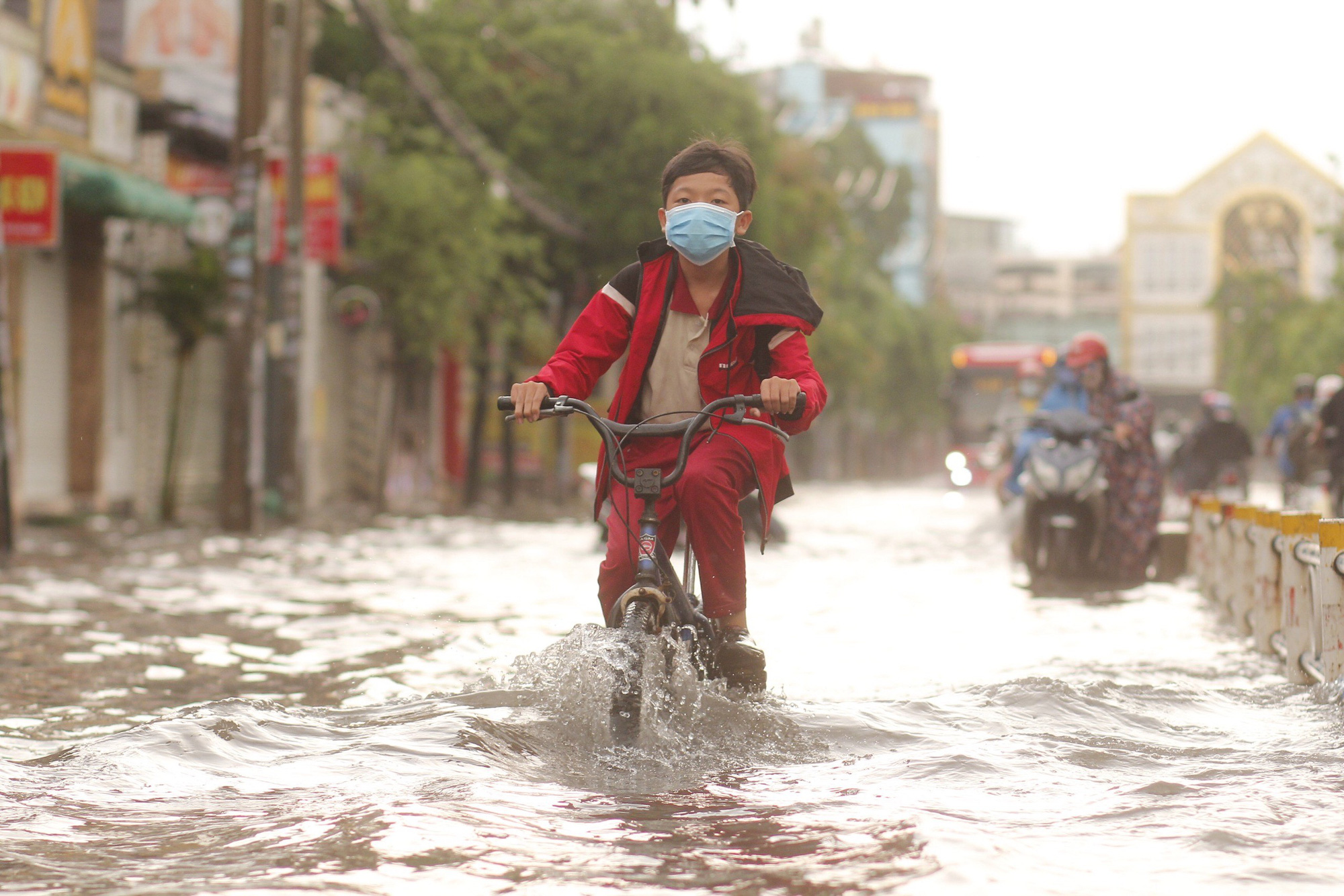 A student rides his bicycle along a flooded street in Ho Chi Minh City, April 16, 2021. Photo: Chau Tuan / Tuoi Tre