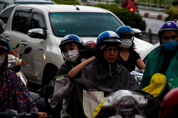 A motorbike driver in Ho Chi Minh City shows exhaustion after being stuck in traffic congestion under the rain. April 15, 2021. Photo: Chau Tuan / Tuoi Tre