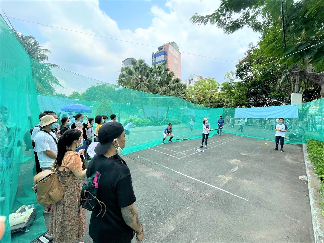 A woman tries playing baseball while others stand around to watch at the Japan Vietnam Festival in Ho Chi Minh City on April 17, 2021. Photo: Dong Nguyen / Tuoi Tre News