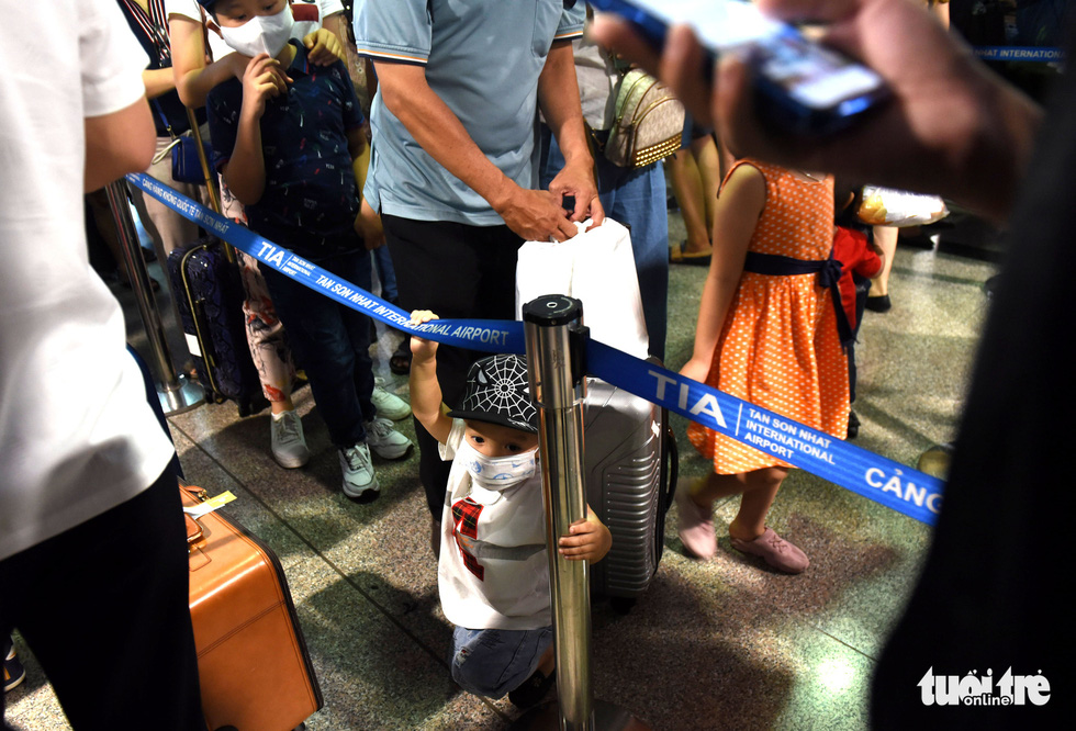 A tired little child stands among the waiting passengers at Tan Son Nhat International Airport in Ho Chi Minh City, April 18, 2021. Photo: Tuoi Tre