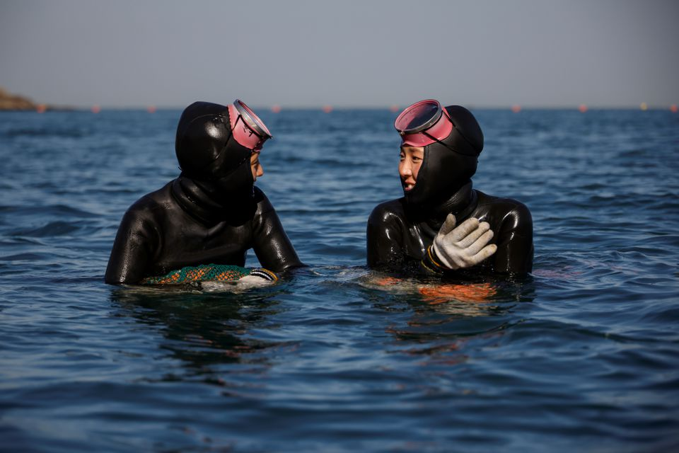 Haenyeo, also known as 'sea women' Jin So-hee, 28, and Woo Jung-min, 35, talk to each other in the sea off Geoje, South Korea, March 30, 2021. Photo: Reuters