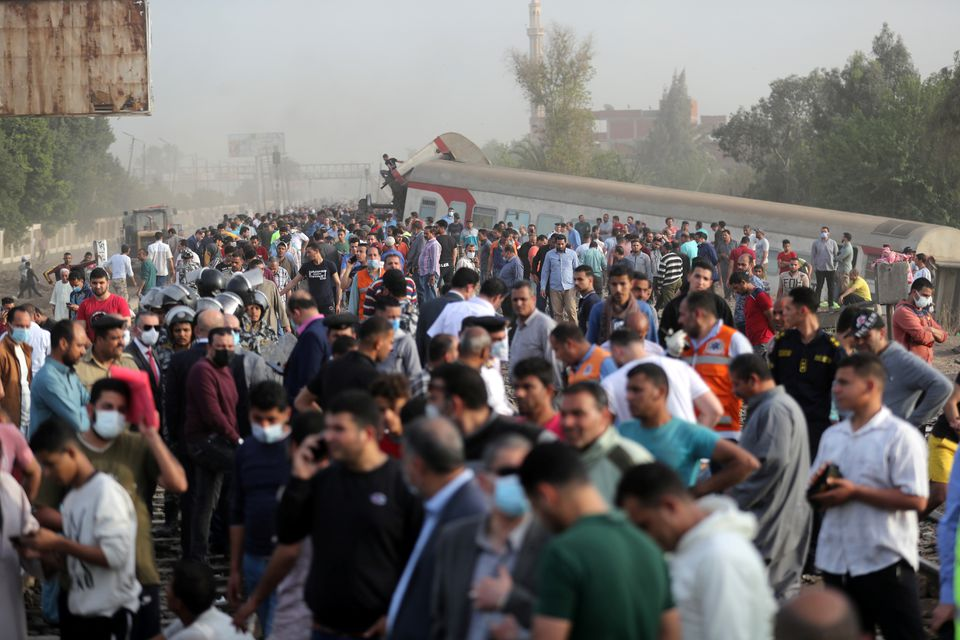 People gather at the site where train carriages derailed in Qalioubia province, north of Cairo, Egypt April 18, 2021. Photo: Reuters