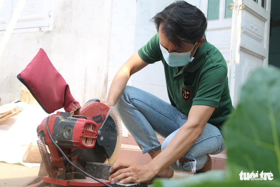 Tran Minh Tan cuts wood with a cutting blade. Photo: Hoang An / Tuoi Tre