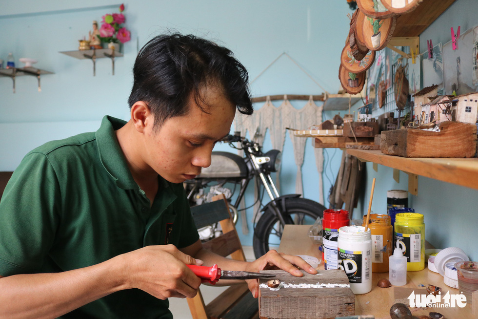 Tran Minh Tan makes miniature from a discarded wood piece in his studio in Dong Nai Province. Photo: Hoang An / Tuoi Tre