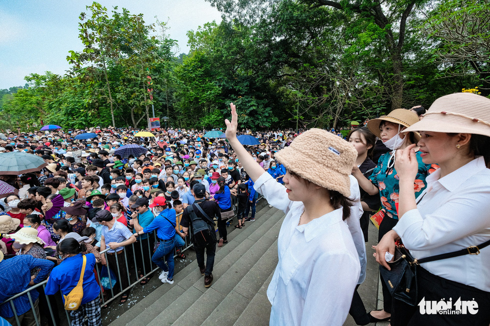 A visitor salutes her acquaintance among the crowd Hung King Temple relic site in Phu Tho Province, Vietnam, April 21, 2021. Photo: Nam Tran / Tuoi Tre