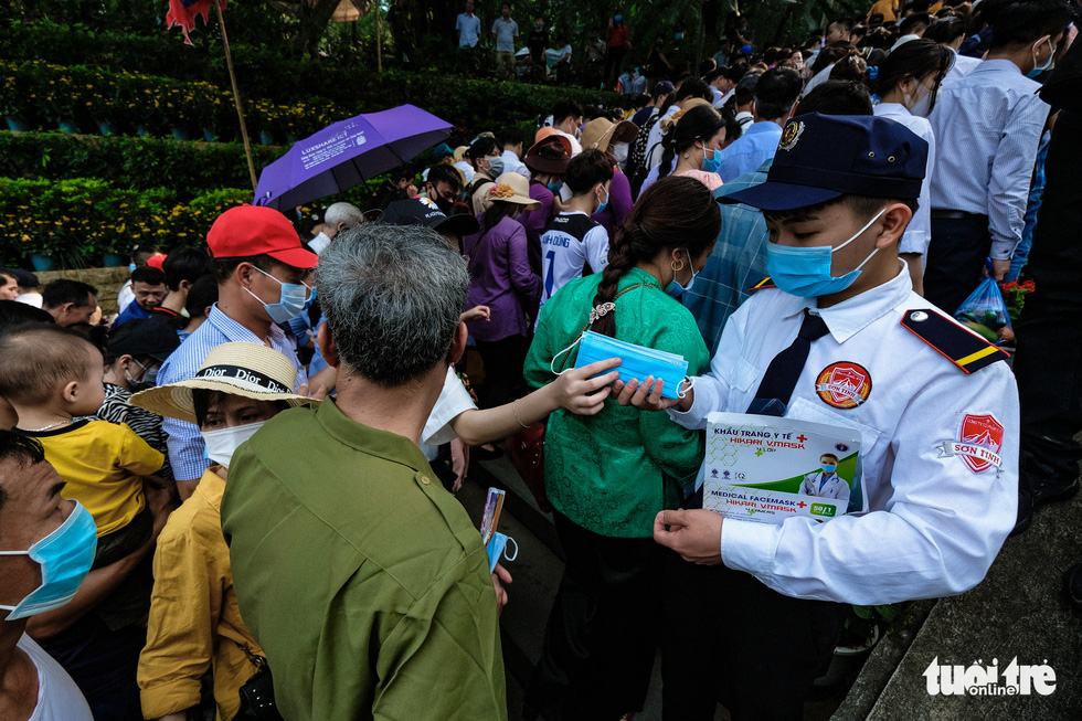 A guard hands out face masks to visitors at the Hung King Temple relic site in Phu Tho Province, Vietnam, April 21, 2021. Photo: Nam Tran / Tuoi Tre