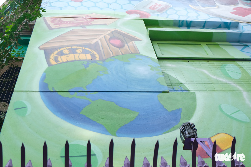 A Vietnamese house sits on the earth in a mural on the wall of a house at the Van Phu residential quarter in Ha Dong District, Hanoi. The painter says this artwork promotes Vietnamese unity in the fight against COVID-19. Photo: Ha Thanh