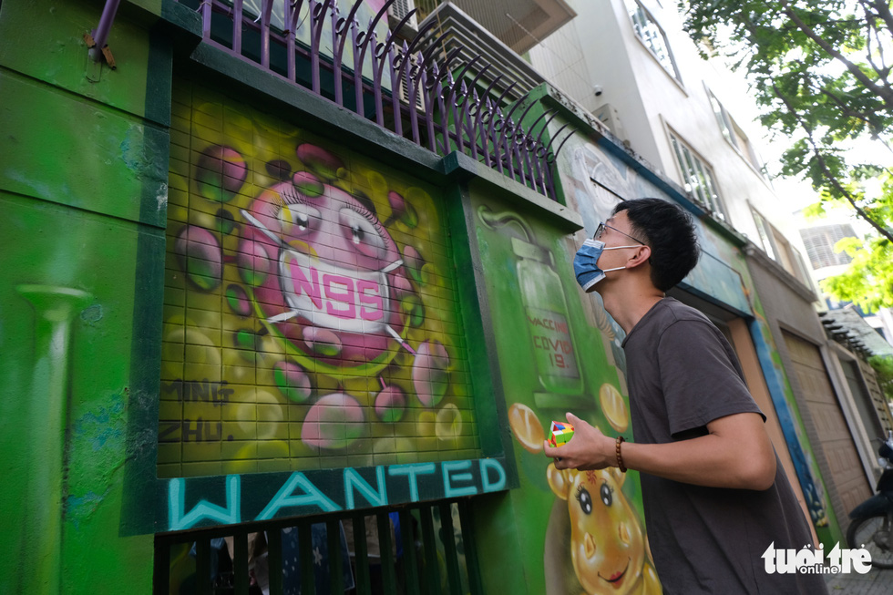 A man looks at a mural on the wall of a house at the Van Phu residential quarter in Ha Dong District, Hanoi. Photo: Ha Thanh