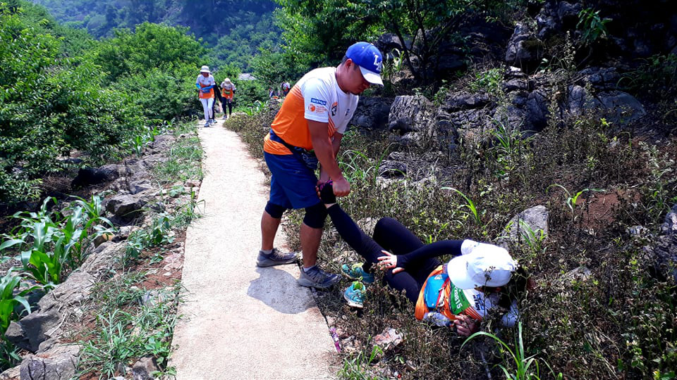 A male runner helps a female competitor suffering a cramp at the 2021 Vietnam Trail Marathon in Son La Province, Vietnam, April 24, 2021. Photo: Khuong Xuan / Tuoi Tre