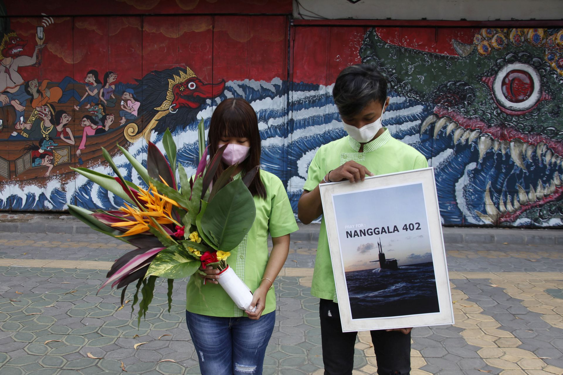 People holding a placard and flowers bow as they pray for the crew of submarine KRI Nanggala-402 which has sunk at the north of Bali sea, during a vigil in Solo, Central Java province, Indonesia, April 25, 2021 in this photo taken by Antara Foto. Photo: Antara Foto/Maulana Surya/ via Reuters