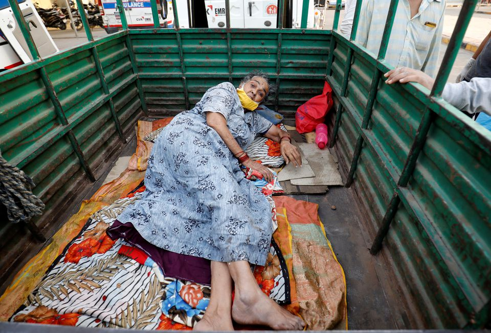 A woman lies in the back of a load carrier waiting to enter a COVID-19 hospital for treatment, amidst the spread of the coronavirus disease (COVID-19), in Ahmedabad, India, April 26, 2021. Photo: Reuters