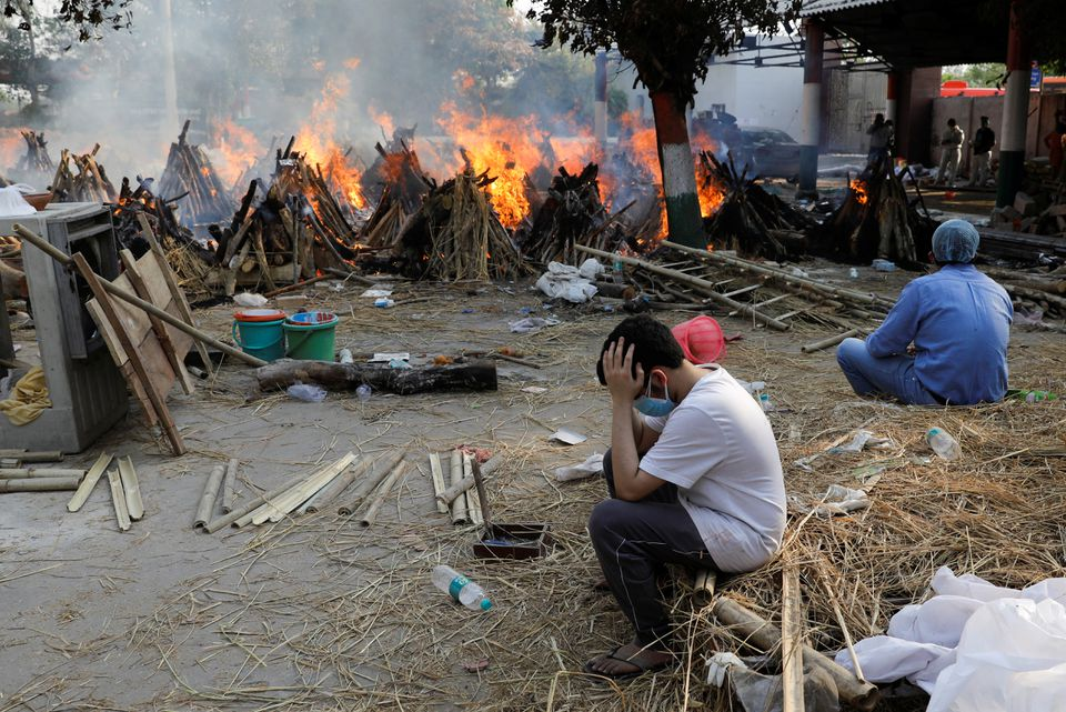 Family members sit next to the burning funeral pyres of those who died from the coronavirus disease (COVID-19), during a mass cremation, at a crematorium in New Delhi, India April 26, 2021. Photo: Reuters