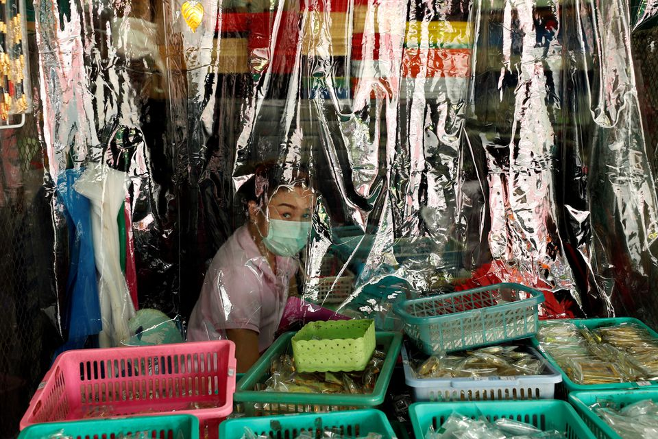 A shopkeeper is seen behind a protecting plastic curtain as the country struggles with a third wave of infections of the coronavirus disease (COVID-19) outbreak in Bangkok Thailand April 26, 2021. Photo: Reuters