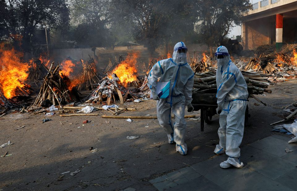 Health workers wearing personal protective equipment (PPE) carry wood to prepare a funeral pyre for a coronavirus disease (COVID-19) victim during a mass cremation at a crematorium in New Delhi, India, April 26, 2021. Photo: Reuters