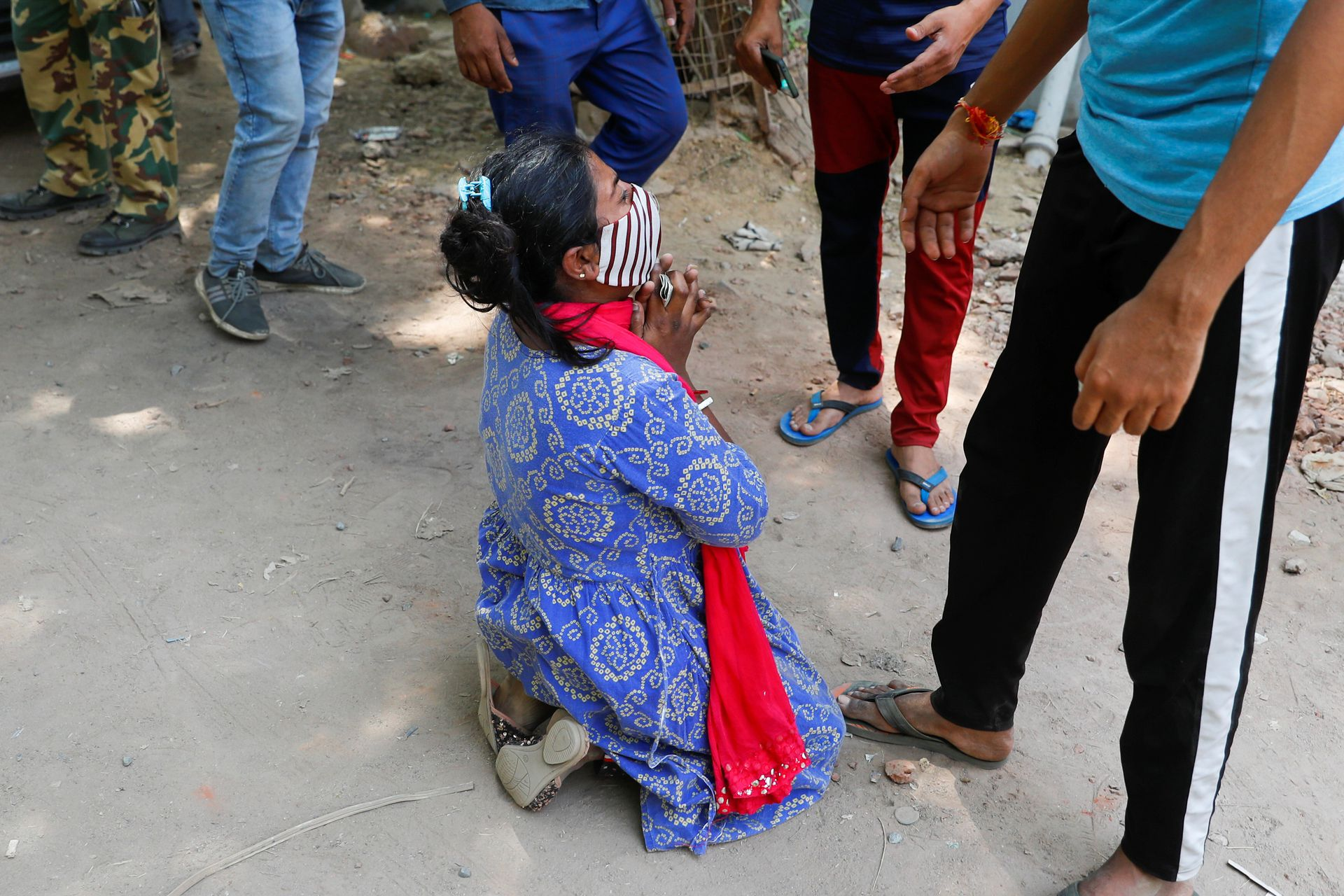 Shruti Saha, who had been waiting since Tuesday night for her turn to get an oxygen cylinder refilled for her mother, reacts after she was informed about her mother's death, outside a refilling workshop, in New Delhi, India, April 28, 2021. Photo: Reuters