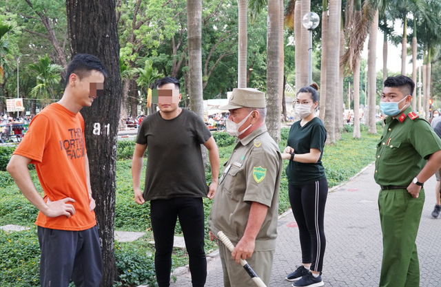 Officers remind two people of wearing face masks at Gia Dinh Park in Phu Nhuan District, Ho Chi Minh City, April 28, 2021. Photo: D.T. / Tuoi Tre