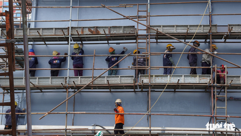 Workers are seen standing on the scaffolding system to pain the hull of the converted vessel Galelian 7. Photo: Hoai Anh / Tuoi Tre