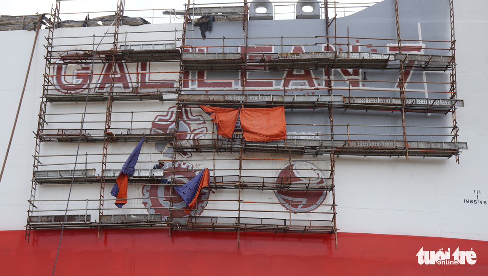 The ship is too tall, making the re-decoration of the name of the ship and the shipyard's logos an uneasy work. Photo: Hoai Anh / Tuoi Tre