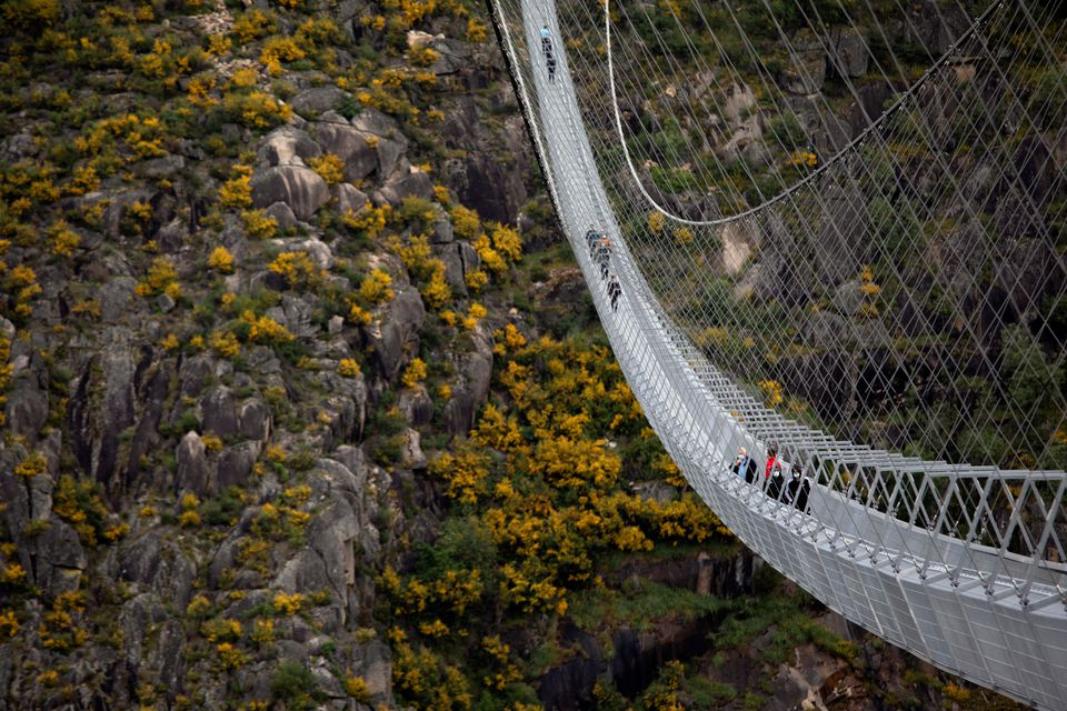 People walk on the world's longest pedestrian suspension bridge '516 Arouca', now open for local residents in Arouca, Portugal, April 29, 2021. Photo: Reuters