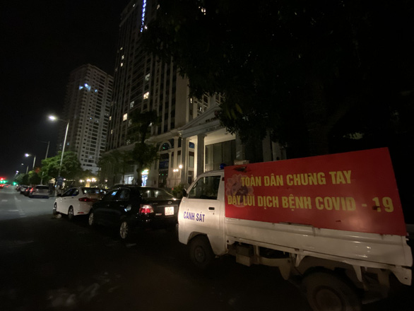 A minitruck of police in Hanoi are seen outside of Florence apartment building on 28 Tran Huu Duc Street, Nam Tu Liem District, where a group of 46 illegal immigrants was detected late on May 2, 2021. Photo: Q.T. / Tuoi Tre
