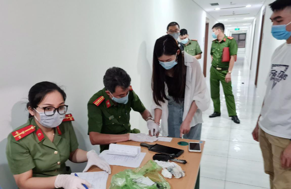 Police officers works to identify putatively illegal immigrants found at on 28 Tran Huu Duc Street, Nam Tu Liem District, Hanoi, May 2, 2021. Photo: Q.T. / Tuoi Tre