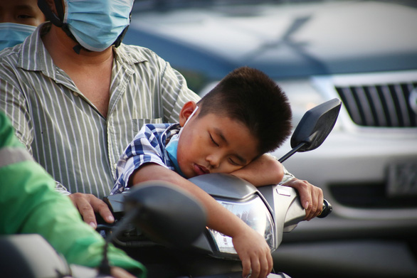 This image shows a boy dozing on the handlebars of a motorbike on the way back to Ho Chi Minh City on May 2, 2021. Photo: Nhat Thinh / Tuoi Tre