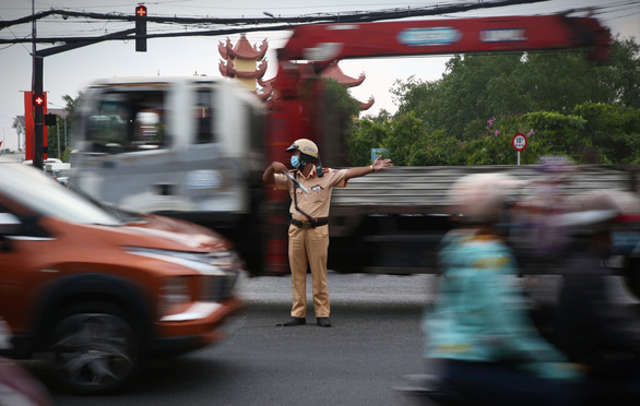 A traffic police officer on duty at a hot spot of traffic on National Highway 1 on May 2, 2021. Photo: Nhat Thinh / Tuoi Tre