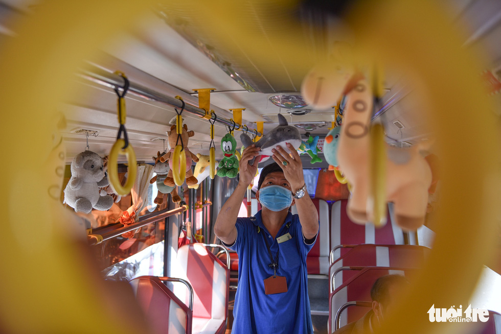 Pham Van Sang, an attendant on bus route No.146 in Ho Chi Minh City, embellishes a coach with plush toys he collected from playing claw machines. Photo: Ngoc Phuong / Tuoi Tre