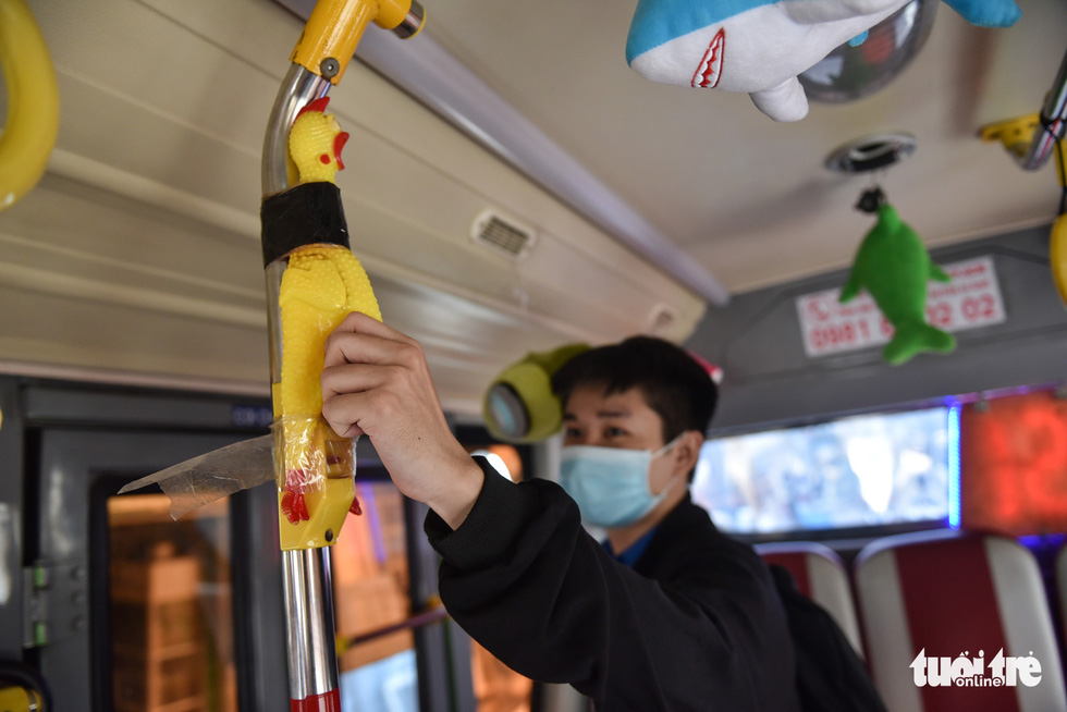 A passenger on bus route No.146 in Ho Chi Minh City signals to get off the vehicle by pressing a toy chicken to make it scream. Photo: Ngoc Phuong / Tuoi Tre