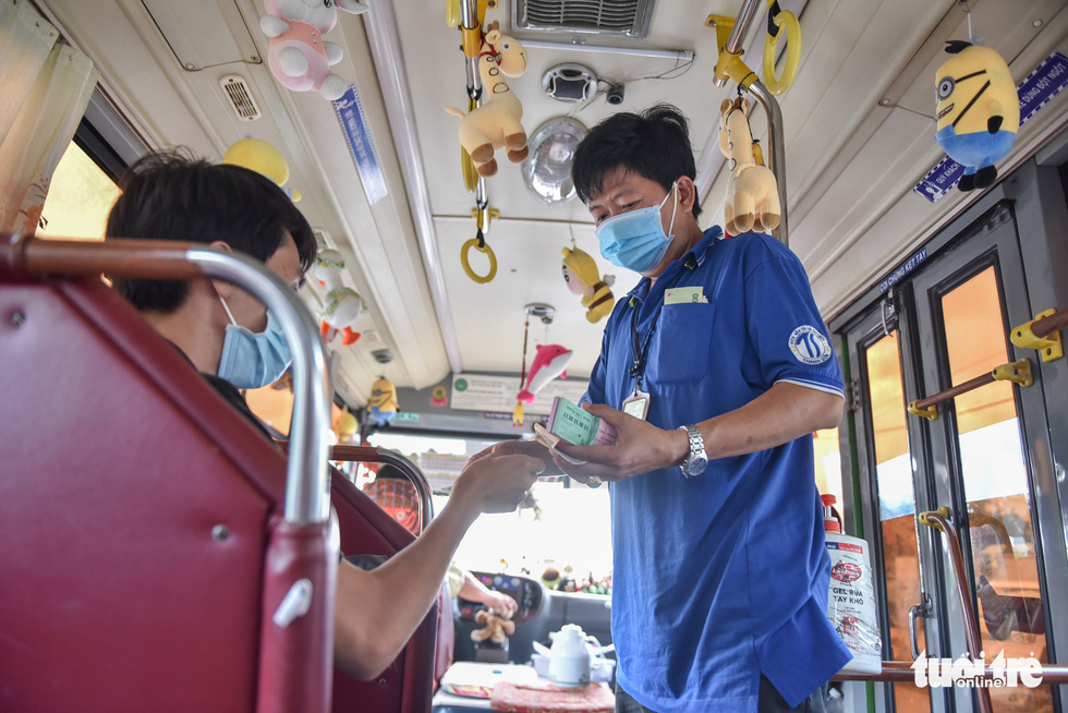 Pham Van Sang works as an assistant on bus route No.146 in Ho Chi Minh City. Photo: Ngoc Phuong / Tuoi Tre