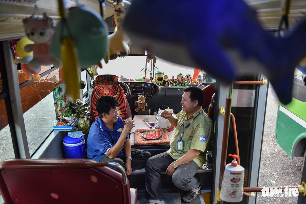 Pham Van Sang sits with Pham Ngoc Tuyen, a bus driver, on a vehicle running bus route No.146 in Ho Chi Minh City. Photo: Ngoc Phuong / Tuoi Tre