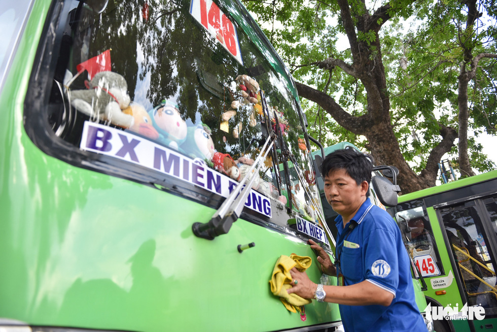 Pham Van Sang, an attendant on bus route No.146 in Ho Chi Minh City, cleans up a vehicle that he works on. Photo: Ngoc Phuong / Tuoi Tre