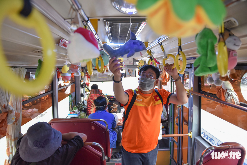 Nguyen Minh Tam, a bus passenger in Ho Chi Minh City, revels in the sight of toys that embellish a vehicle running bus route No.146 in the city. Photo: Ngoc Phuong / Tuoi Tre