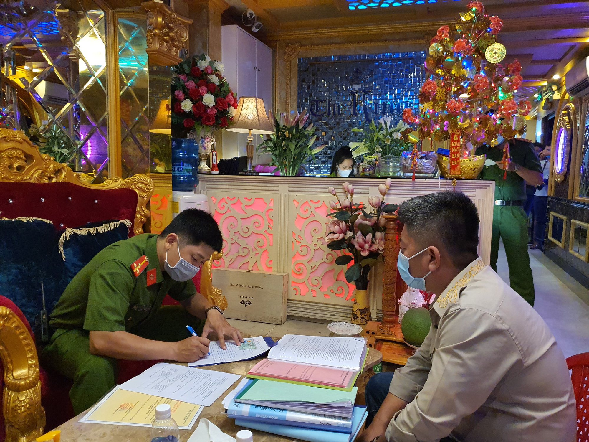 A police officer works with a representative of The King Restaurant in District 1, Ho Chi Minh City, May 4, 2021. Photo: D.T. / Tuoi Tre