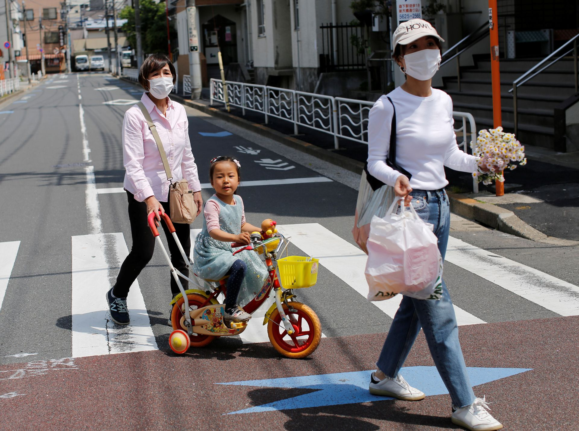 Tami Shimada, 69, a member of a senior cheer squad called Japan Pom Pom, walks home from the park with her granddaughter Elisa, 4, and daughter-in-law Tomoko, 44, in Tokyo, Japan, April 25, 2021. Photo: Reuters