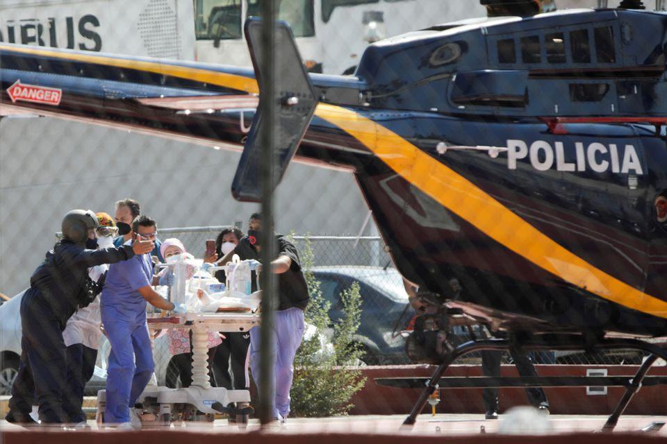 Paramedics transport Brandon Giovani Hernandez, who was injured during the accident where an overpass of the metro partially collapsed with train cars on it at Olivos station, toward a helicopter as he is transferred to another hospital, in Mexico City, Mexico May 4, 2021. Photo: Reuters