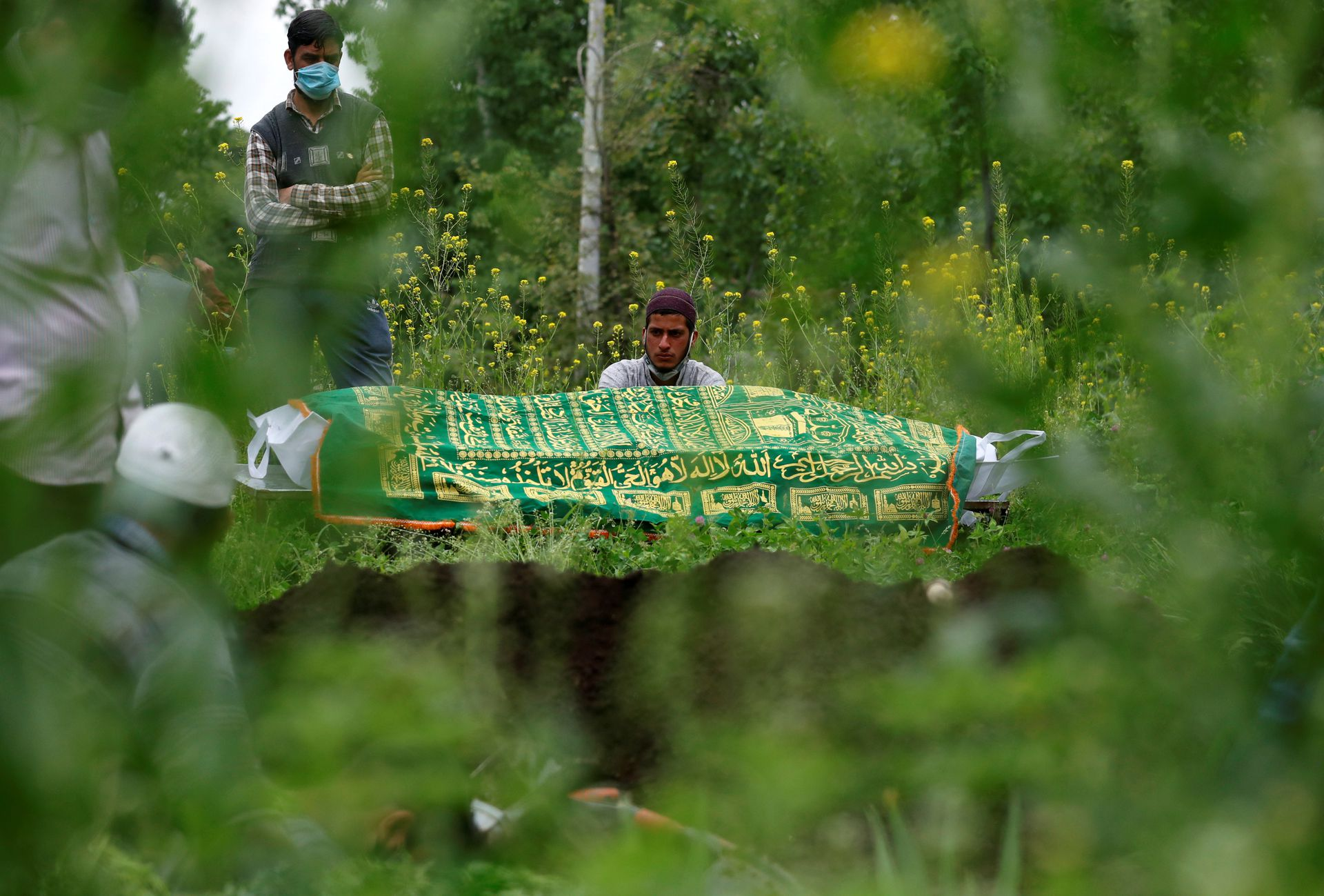 Relatives are seen next to the body of a man who died due to the coronavirus disease (COVID-19), as they wait for a grave to be prepared for his burial at a graveyard on the outskirts of Srinagar May 4, 2021. Photo: Reuters
