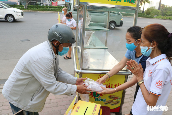 A needy worker gets a free sandwhich in from two members of the Phat Tam club. Photo: Hoang An / Tuoi Tre