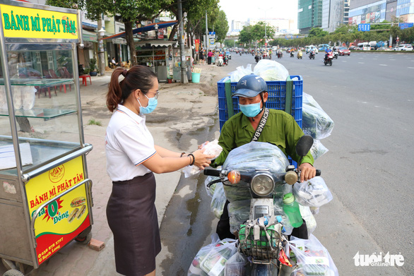 A Phat Tam member gives a free sandwich to a laborer.  Photo: Hoang An / Tuoi Tre