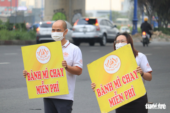 Mai Anh and Anh Tuan dance with a sign to catch the passersby. Photo: Hoang An / Tuoi Tre
