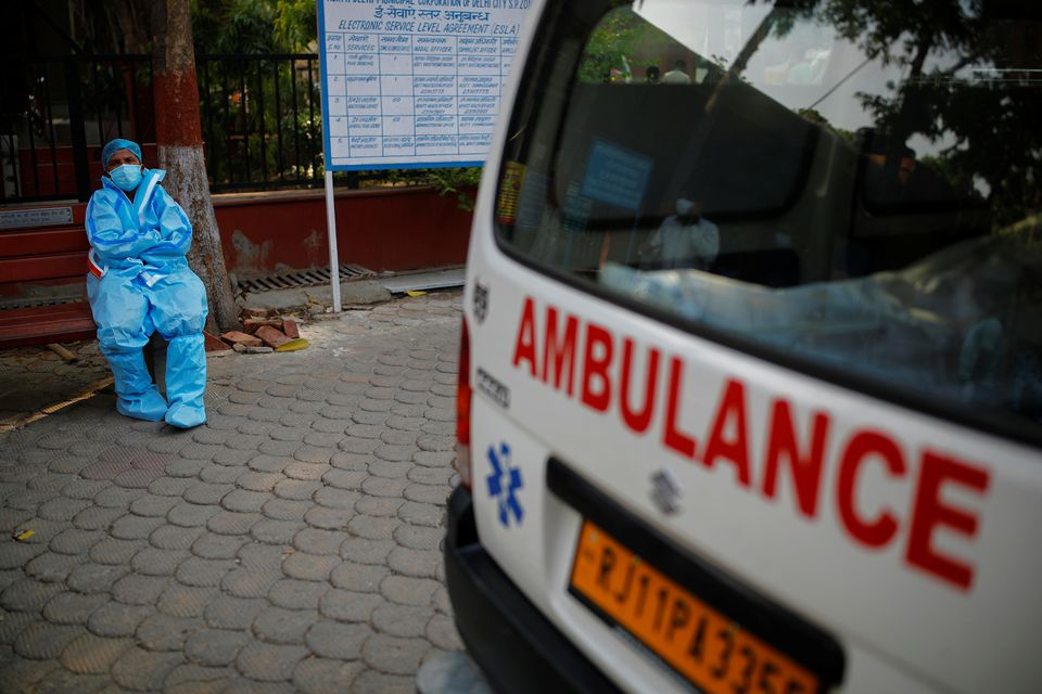 A health worker rests as he sits next to his ambulance carrying a dead body of a victim who died due to the coronavirus disease (COVID-19), at a crematorium in New Delhi, India, May 10, 2021. Photo: Reuters