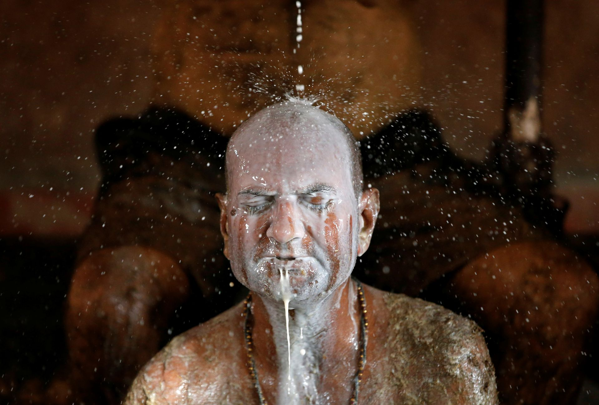 Ashok Oza bathes in cow milk to remove cow dung from his body during 'cow dung therapy', believing it will boost his immunity to defend against the coronavirus disease (COVID-19) at the Shree Swaminarayan Gurukul Vishwavidya Pratishthanam Gaushala or cow shelter on the outskirts of Ahmedabad, India, May 9, 2021. Photo: Reuters