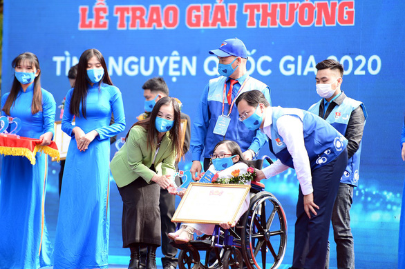 Nguyen Thi Ngoc Tam (sitting in the wheelchair) is conferred with the National Volunteering prize in 2020 for her decades-long philanthropic education activities. Photo: Duong Trieu / Tuoi Tre
