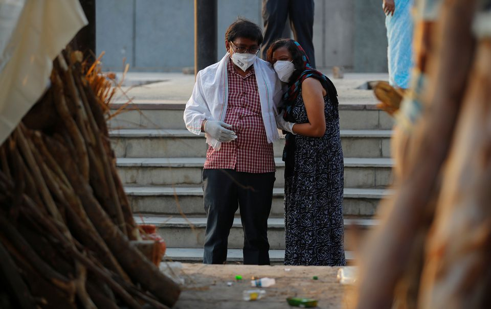 A couple mourns as they stand next to the funeral pyre of a relative who died due to the coronavirus disease (COVID-19), at a crematorium in New Delhi, India, May 10, 2021. Photo: Reuters