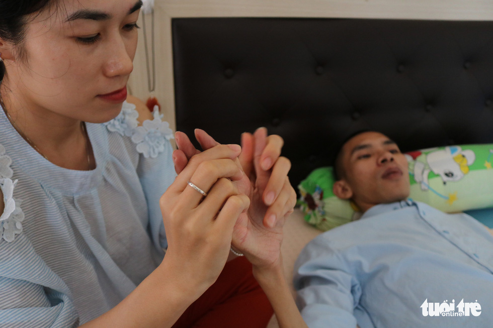 Truc massages Tin's hand after he spent hours in bed at their home in District 7, Ho Chi Minh City, Vietnam. Photo: Hoang An / Tuoi Tre