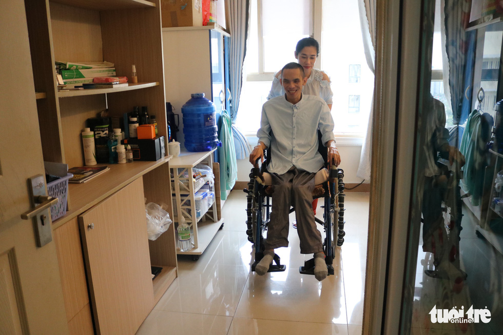 Truc guides Tin's wheelchair in their home in District 7, Ho Chi Minh City, Vietnam. Photo: Hoang An / Tuoi Tre