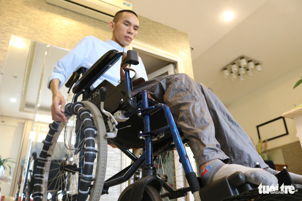 Tin pushes his wheelchair in his home in District 7, Ho Chi Minh City, Vietnam. Photo: Hoang An / Tuoi Tre