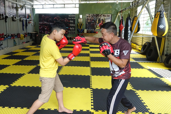 Nguyen Tri Dung and his father, Nguyen Phu Cuong, practice boxing in their private martial arts center. Photo: Hoang Tung / Tuoi Tre