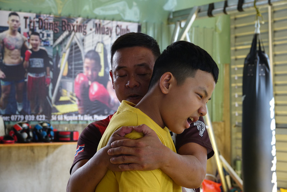 Nguyen Tri Dung's father helps to deal with ligament pain in his right arm. Photo: Hoang Tung / Tuoi Tre